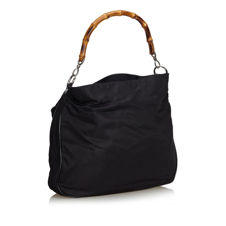 This satchel features a canvas body, bamboo top handles, flat patent leather strap, open top, interior zip compartment and interior zip and slip pockets. It carries as B+ condition rating.  Inclusions:  This item does not come with
