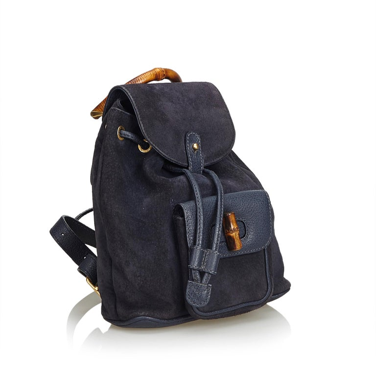This backpack features a suede body, flat leather back straps, bamboo top handle, top flap with button closure, drawstring closure, exterior flap pocket with bamboo twist lock closure, and an interior zip pocket. It carries as B+ condition