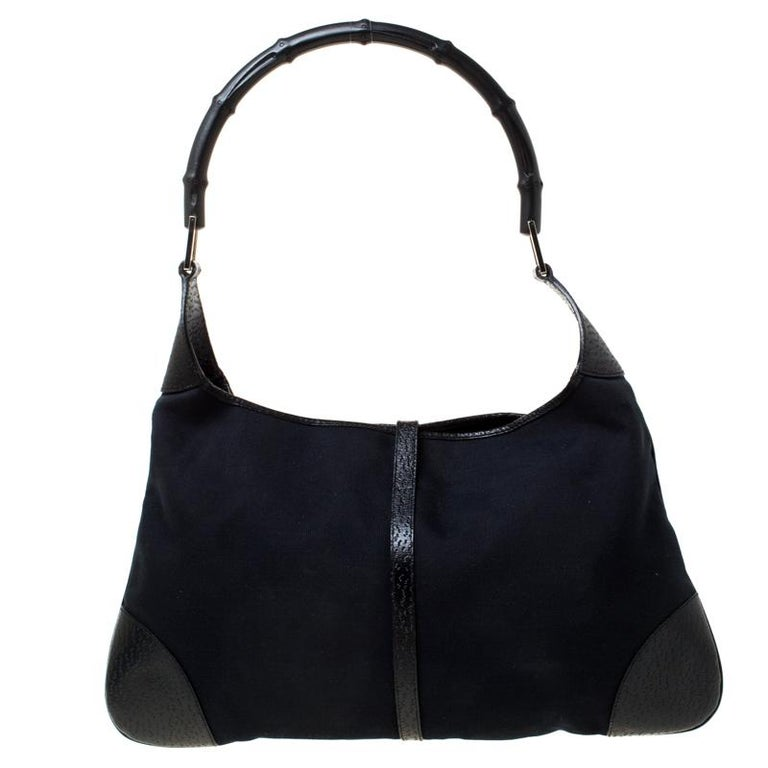 This Gucci bag will never fail you. Crafted from canvas and leather in Italy, this gorgeous number has the signature closure in silver-tone that opens up to a spacious nylon interior. Complete with a single bamboo handle, this bag is ideal for