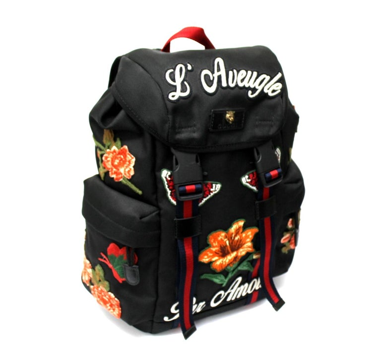 Gucci backpack, made of black canvas with floral patches and silver hardware.  The backpack is equipped with a snap hook closure, internally lined in waterproof fabric, quite roomy.  It also features two padded handles, a central handle and two side