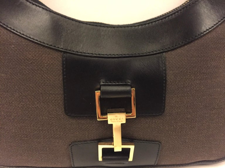 """- Gucci black leather and brown canvas hobo style bag.   - Zip closure.   - """"GG"""" lining interior.   - Measurements: 28cm x 20cm x 2cm. Drop: 28cm.   - This item is unused!"""