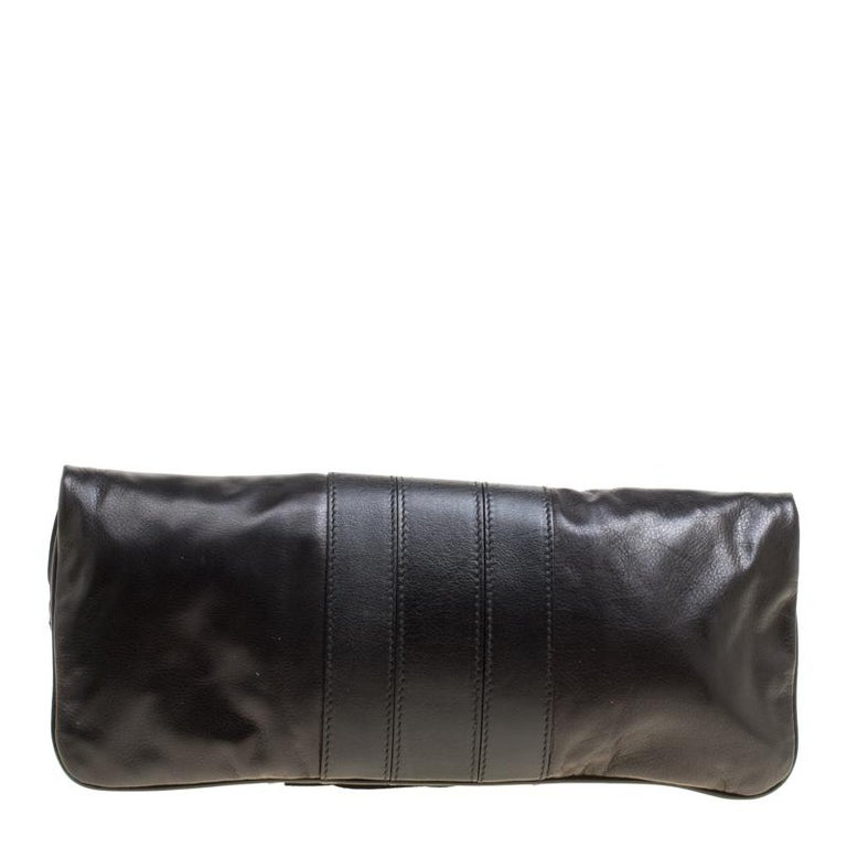 Have all eyes on you when you flaunt this stunner of a clutch by Gucci. Crafted from leather, it carries a black shade and a fold over style with a bamboo turn-lock and a zipper with a bamboo tassel pull. A well-sized nylon interior completes this