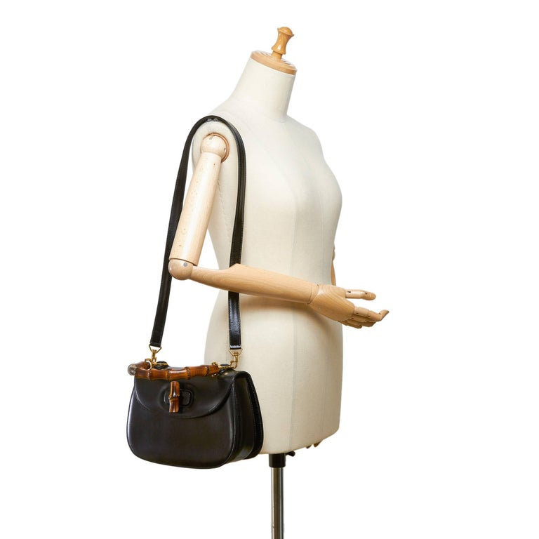 - Vintage Gucci black leather bamboo handle bag with a detachable shoulder strap.   - Featuring bamboo bullet and twist lock closure, and interior zip and slip pocket.  - Size: 18cm x 27cm x 8cm.   - Included: Dust Bag, Mirror. Shoulder Strap.    -