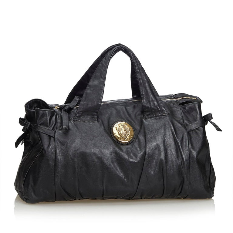The Hysteria features a leather body, leather handles, gold-tone hardware, a top zip closure, and an interior zip pocket. It carries as B+ condition rating.  Inclusions:  This item does not come with inclusions.  Dimensions: Length: 24.00 cm Width: