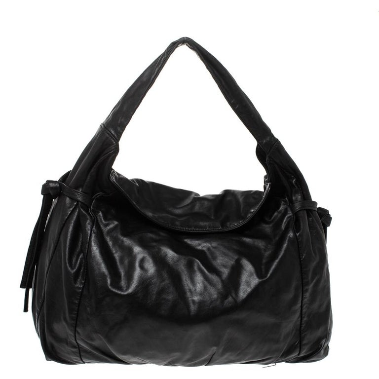 This Gucci hobo is built for everyday use. Crafted from leather, it has a black exterior and a single handle for you to easily parade it. The nylon insides are sized well and the hobo is complete with the signature emblem at the front.  Includes: