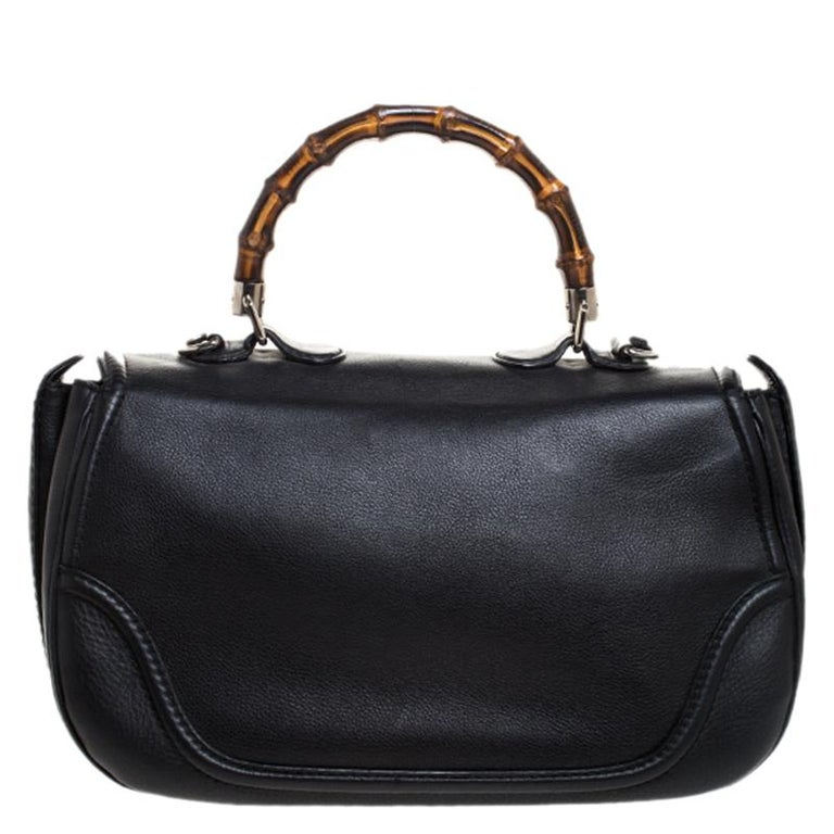 Add a touch of artistic blend to your outfit with this Gucci bag. Crafted with Gucci's classic bamboo detailing, this black bag is a timeless piece. It features a leather exterior with a bamboo detailed handle, twist-lock closure and tassels on one