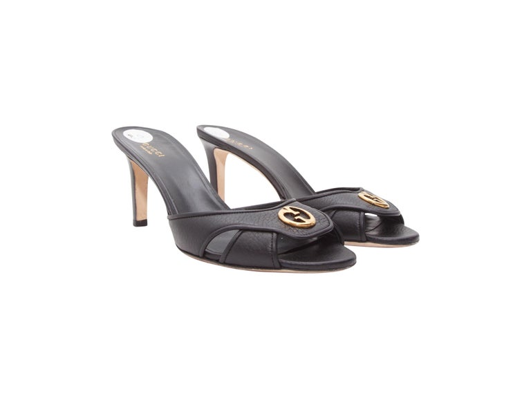 Product details:  Black leather mule kitten heels by Gucci.  Logo detail accents vamp.  Open toe.  Slip-on style.  Goldtone hardware.  3