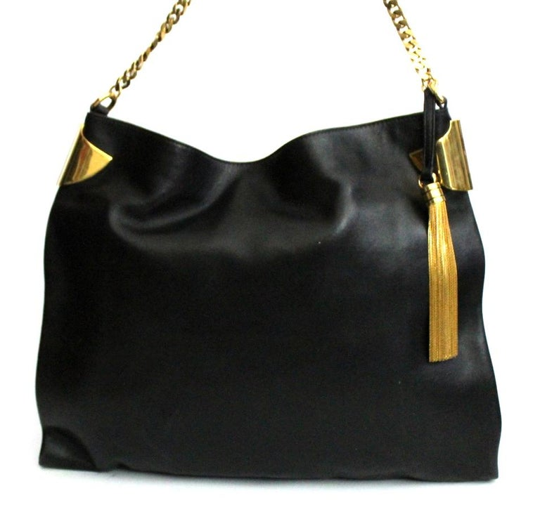 Beautiful and elegant Gucci bag in soft black leather with gold hardware. Equipped with a chain handle to wear it comfortably on the shoulder. Enriched on the front by a charms. The bag has a button closure, internally large and equipped with