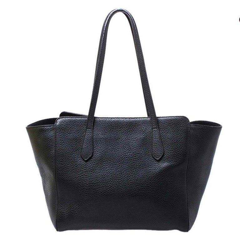 High on appeal and style, this tote is a Gucci creation. It has been crafted from leather in Italy and shaped to exude class and luxury. The bag comes with two handles, a spacious canvas interior, and the brand label on the front. This tote is ideal