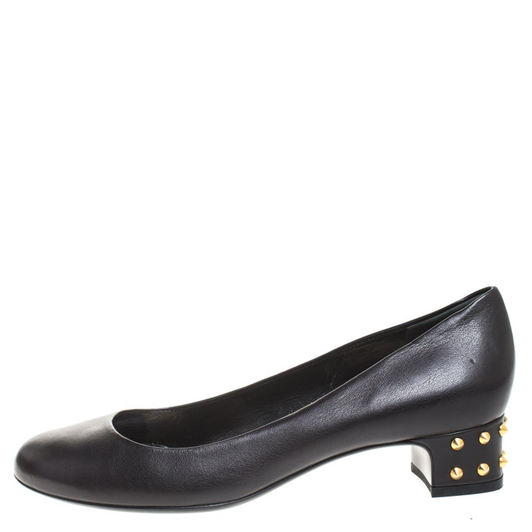 Boost your style quotient when you wear these pumps from the house of Gucci. Crafted from leather, they feature round toes and spike studs on the short block heels. Add a touch of classic glamour to your look by wearing these black pumps.  Includes: