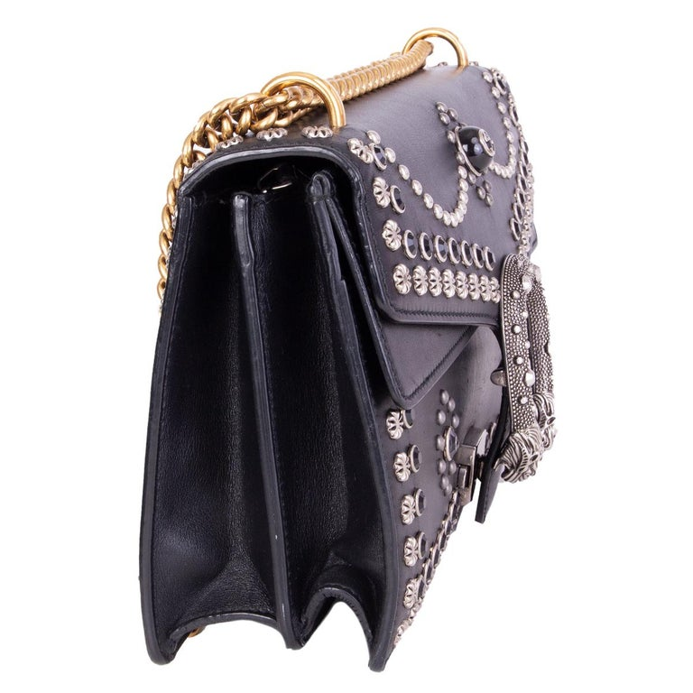 Gucci 'Small Studded Dionysus' shoulder bag crafted in black studded calfskin embellished with silver-tone studs and black crystals. Features a gold-tone chain link shoulder strap and textured tiger head push-pin closure. Lined in pale pink