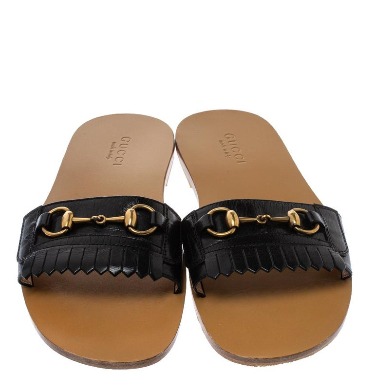 These pretty slides sandals are just the ideal choice for a relaxed day out. The flats are crafted from black leather and accented with fringe details and the signature Horsebit motif in gold-tone metal on the front strap. They are complete with