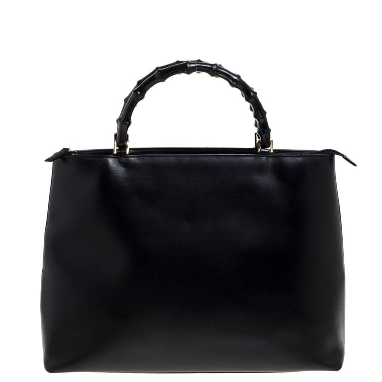This Gucci tote is sure to keep you fashion-forward. Designed out of black leather, this bag comes with two bamboo handles. It comes with protective metal base studs in gold-tone hardware. The interior of this Italian-made piece is spacious to carry