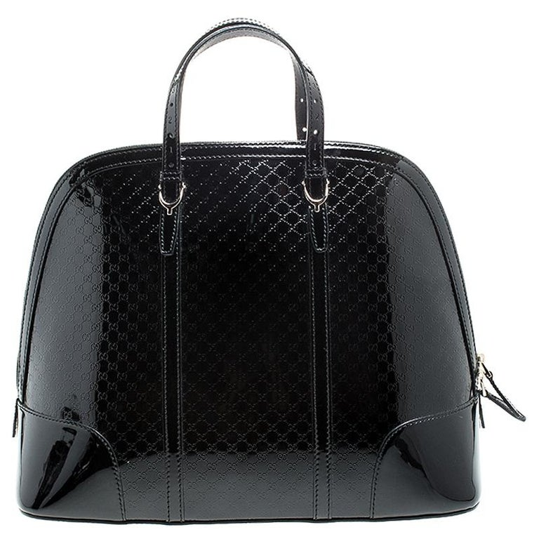 This stylish Nice satchel from Gucci is crafted from Microguccissima patent leather. The bag has a feminine silhouette and comes with dual top handles and protective metal feet at the bottom. The dual zip closure opens to a canvas-lined interior