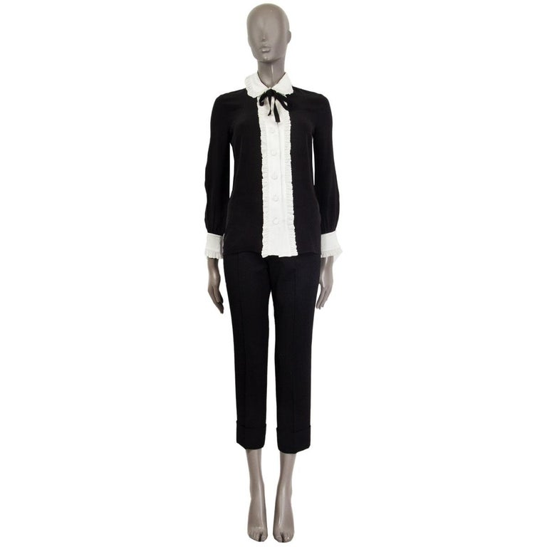 100% authentic Gucci ruffled blouse in black&white silk (missing content tag) with a black ribbon at the neck-line. Closes with eight buttons on the front and has ruffles on the collar-hem, along the front and on the cuffs-hem. Unlined. Has been