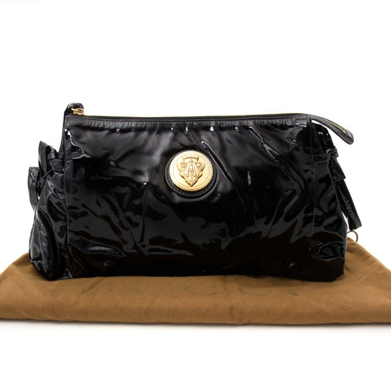 In excellent condition   Gucci Black Patent Leather Clutch  This shiny black clutch is big enough for all your personal belongings. The gold-toned hardware gives the bag an exclusive look.  Comes with:  booklet dust bag