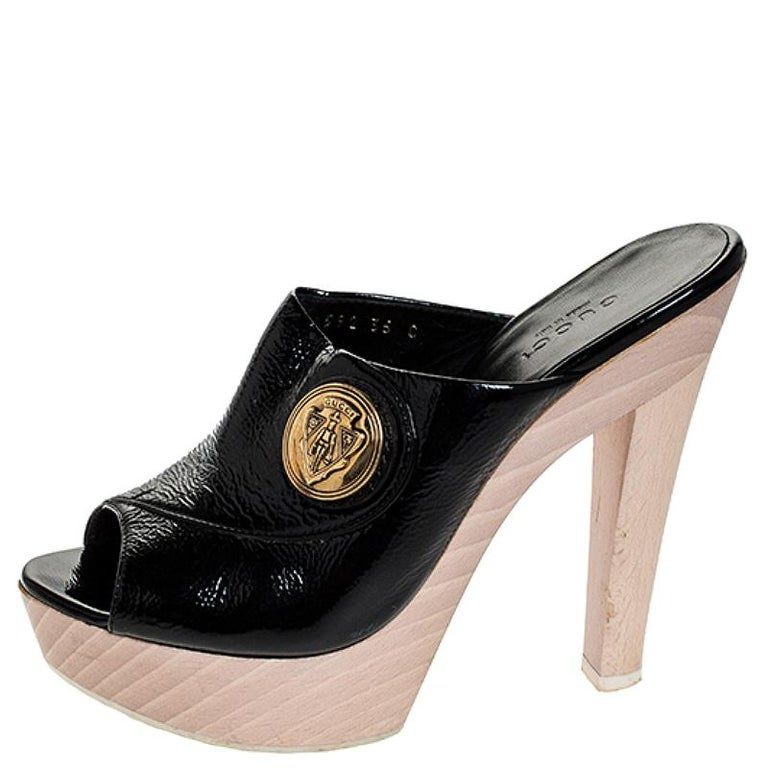 These Gucci Hysteria platform clogs are comfortable and stylish. They have been crafted in Italy and are made from patent leather in black. They have an open toe silhouette, platforms and 13 cm heels. They come with leather lining and feature the