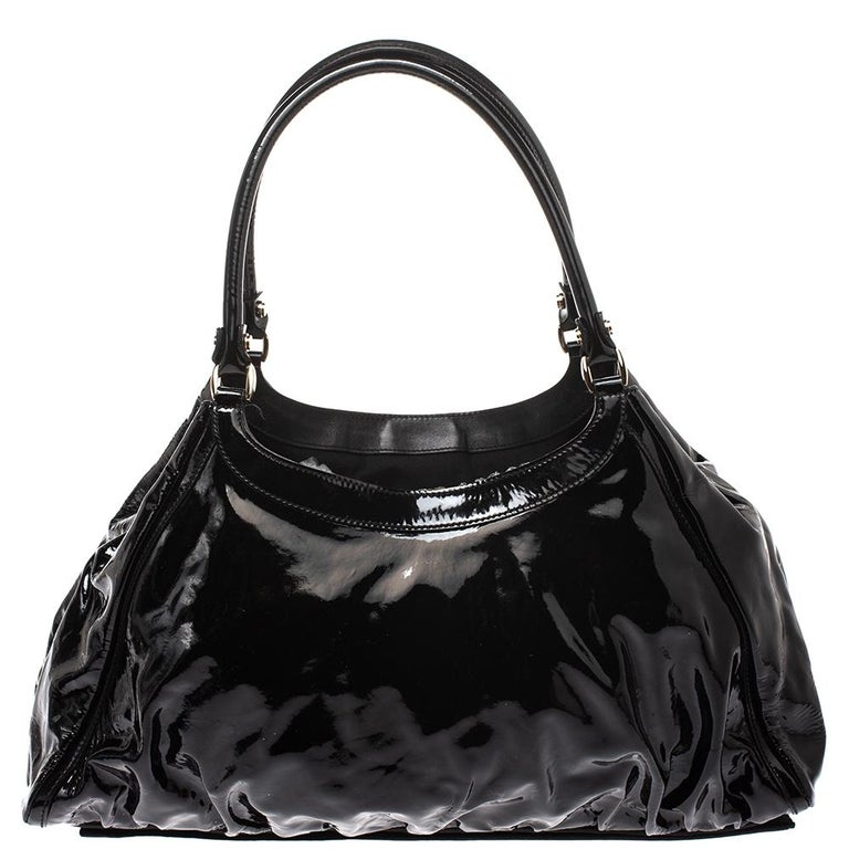 Gucci brings to you this amazing D Ring hobo that is smart and modern. Made in Italy, this black hobo is crafted from glossy leather and features a single top handle and a D shaped ring at the front. The zip fastening at the top reveals a