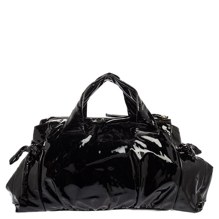 This Gucci tote is built for everyday use. Crafted from patent leather, it has a black exterior and two handles for you to easily parade it. The nylon insides are sized well and the tote is complete with the gold-tone signature emblem.  Includes: