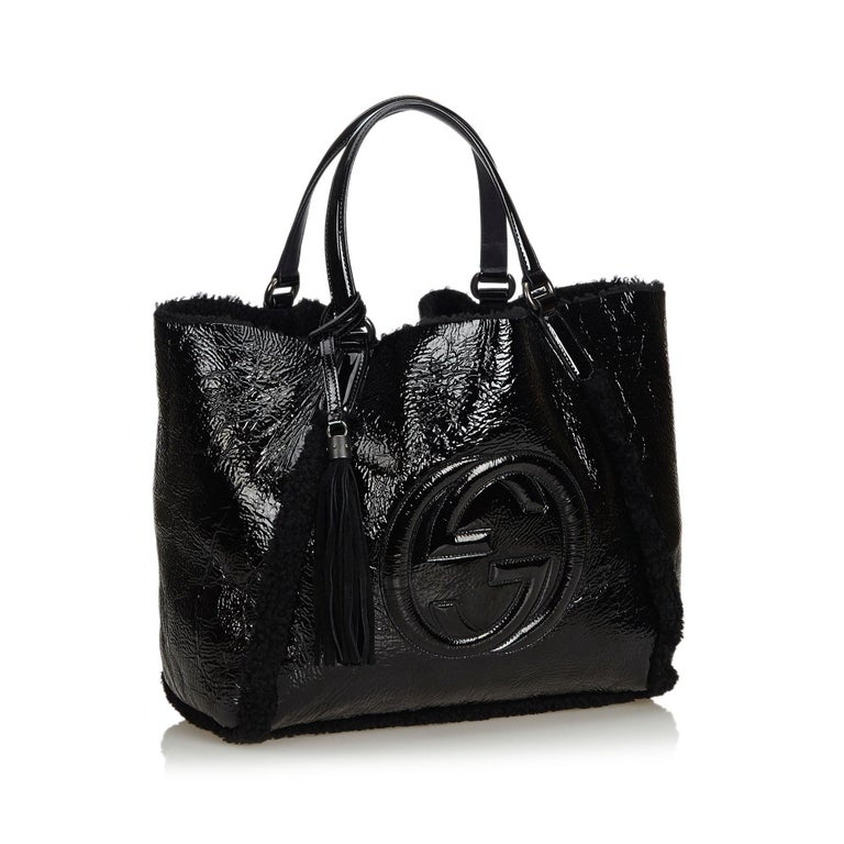 The Soho features a patent leather body, mouton interior, flat leather handles with tassel details, and an open top. It carries as AB condition rating.  Inclusions:  Dust Bag Pouch  Dimensions: Length: 31.00 cm Width: 34.50 cm Depth: 18.00
