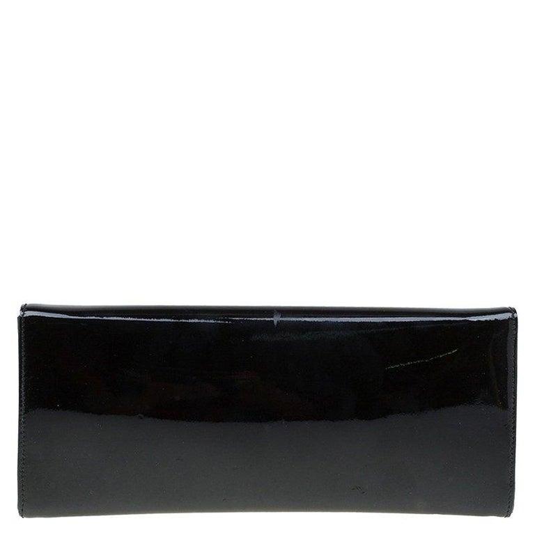 Dress to impress with this stylish clutch from Gucci. Crafted from patent leather the clutch comes with a tempered glass front and 4 studs on each corner. It opens to a leather lined interior and can easily fit inside your tote.  Includes: Original