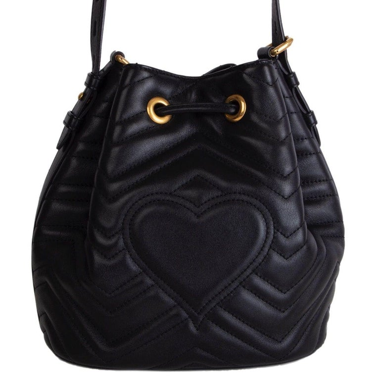 Gucci GG Marmont Matelasse bucket bag in black quilted leather with detachable leather strap and striped web strap. Closes with a drawstring on top. Lined in pink suede with an open pocket against the front and back. Has been carried and is in