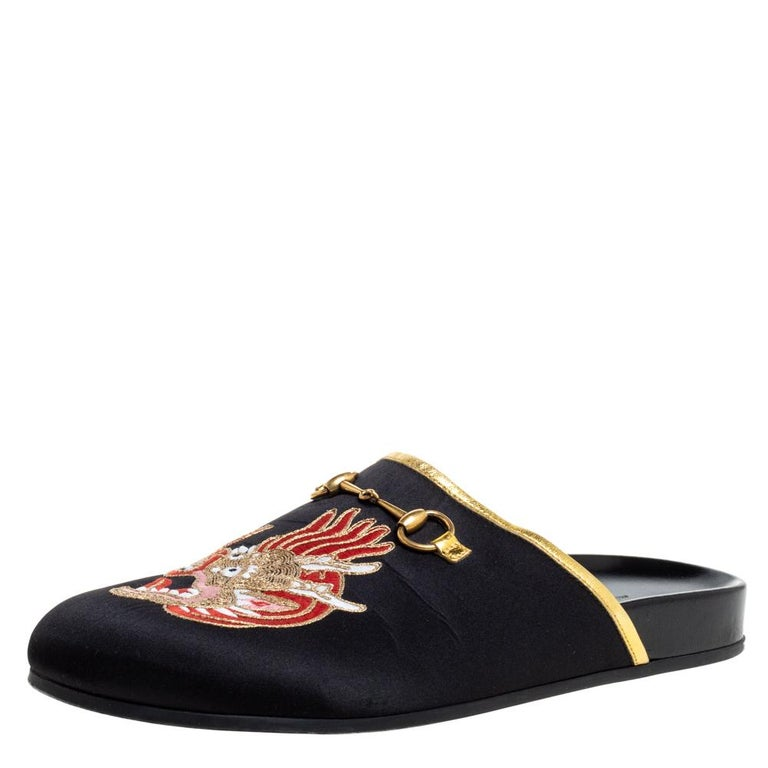 Beautifully designed, these mules from Gucci are truly charming! They are crafted from black satin and styled with an open back silhouette. They exhibit dragon embroidered and Horsebit detailed vamps and come endowed with comfortable leather-lined