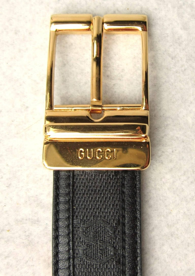 Gucci Black with Gold Tone Belt Buckle. Signature GG on the canvas with leather trim. This was purchased in the early 90s and still has the tag on it. Labeled a size 44 - Measures 1.15 inches wide. First belt hole is at 41 inches and the belt is 47