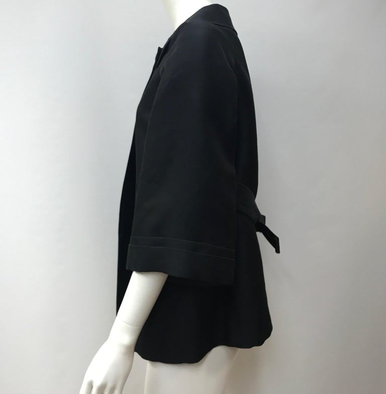 Gucci Black Silk Cape Jacket-42. This amazing Gucci cape jacket is in good condition. It only shows use to the underarms with slight staining, as shown in picture. It is made of black silk throughout. The sleeves are quarter length and there is a