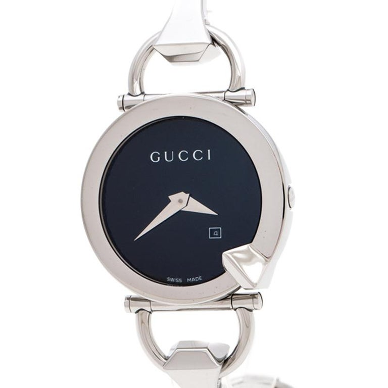 This classy Gucci watch combines beauty and femininity. Its round case features a well-designed bezel. The black dial is combined with silver-tone hands and its minimalist style is taken further with a petite date window. The link bracelet is made
