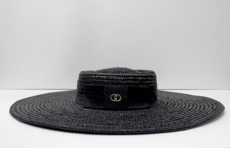 A true one of kind piece from the Gucci archives! Circa 1980s, this limited edition wide brim black Gucci straw hat features a black ribbon bow with a gold GG logo. The bow is to be worn in the back, hat look best tilted to one-side. Perfect to pair