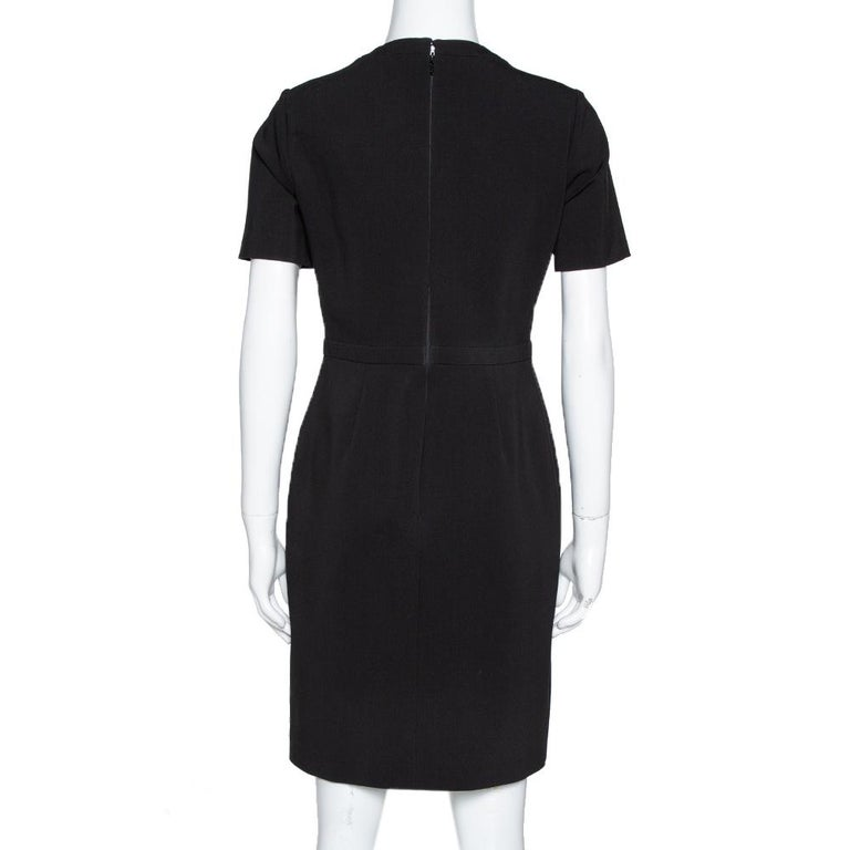 Style this black dress with the right accessories for an impeccably fashionable look. Beautifully tailored to offer you the best fit, this Gucci dress has short sleeves, a nipped-in waist, buckle details on the front and a back zipper.