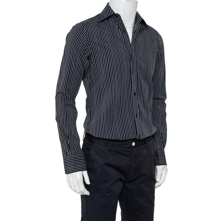 A seamless blend of comfort, class, and style, this Gucci shirt is ideal for those office meetings and formal settings. Tailored from cotton in a black shade, the creation is detailed with stripes all over, cuffed long sleeves, and a classic
