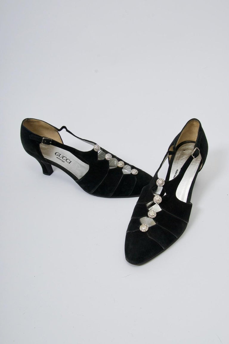 Vintage Gucci evening shoes in black suede adorned with round rhinestone buttons at the cut-our T-strap form. Narrow black leather border edging. Low heel provides a level of comfort to these elegant shoes. Approximate size 7.