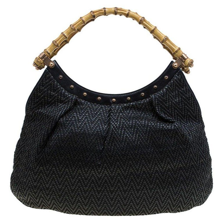 Introduced by the house of world's leading luxury brands, Gucci, this hobo is versatile, stylish and highly utilitarian. Crafted in black woven leather, this bag comes with a dual bamboo top handle and decorated with golden studs. It opens to a