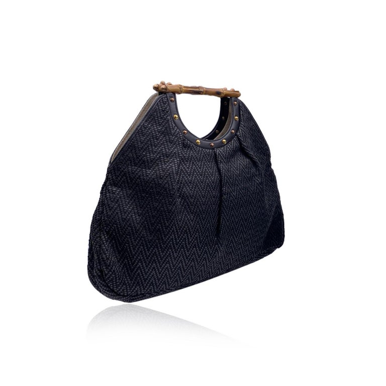 Beautiful Gucci Bamboo tote bag in black color. Crafted from woven leather and thread, with chevron pattern. Double distinctive Bamboo handle. Gold metal studs on the front and on the back. Open top. Beige fabric lining. 1 side zip pocket