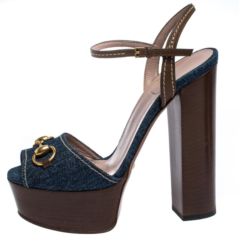 How lovely are these sandals from Gucci! They've been beautifully crafted from denim and leather and styled with Horsebit accents on the uppers. They carry open-toes, ankle straps and 15.5 cm block heels supported by platforms. Let this pair lift