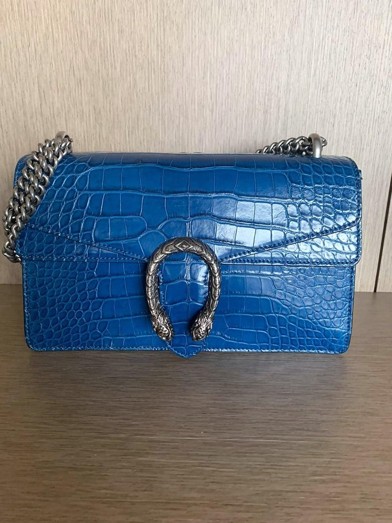 Amazing and super rare Gucci crocodile bag Model Dyonisus, year 2016 Color Agata Blue Real crocodile Palladium tone hardware Tiger head pin closure with side release Hand painted borders Sliding chain strap, can be worned as shoulder strap or as top