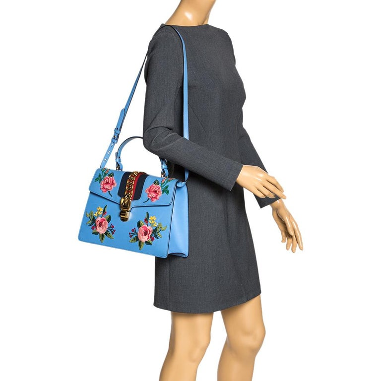 From the house of Gucci comes this gorgeous Sylvie bag that will perfectly complement all your outfits. It has been luxuriously crafted from blue leather and styled with floral embroidery on the front, chain-web decorated flap, and a buckle lock