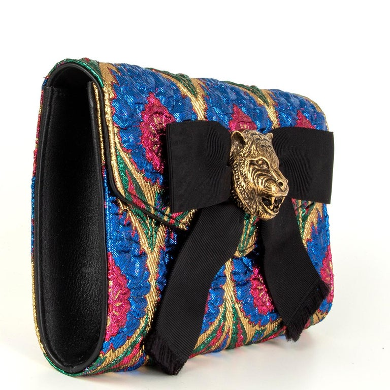 Gucci 'Animalier Broadway' clutch in pink, blue, gold and green brocade. Opens with a magnetic closure and is lined in black and tan lambskin with one open pocket against the back. Antique gold-tone feline head and black gros grain bow detail. Has
