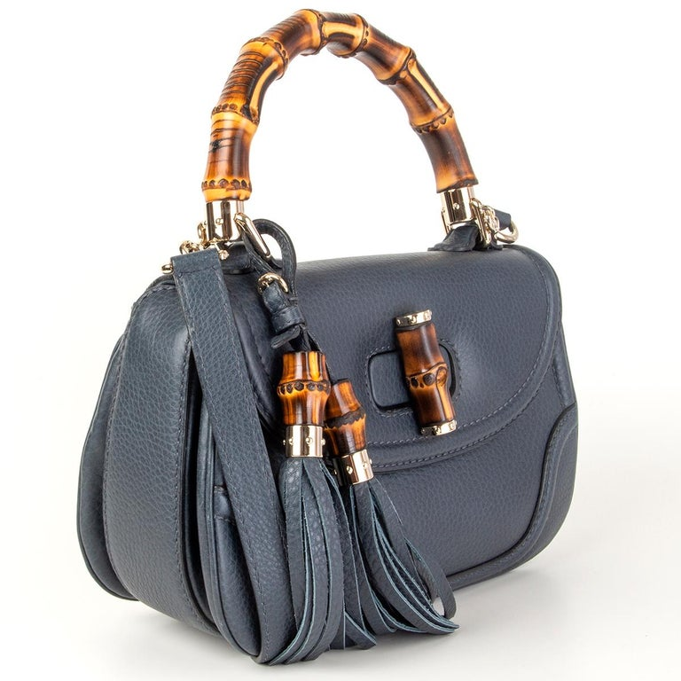 Gucci 'New Bamboo Medium' top-handle shoulder bag in navy blue grained calfskin. Opens with a bamboo turn-lock and is lined in off-white suede with one zip pocket against the back and one open pocket against the front. Comes with a detachable