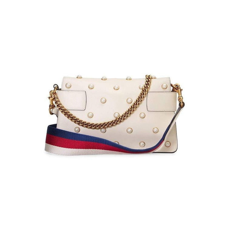 A chain clutch with all over pearl studs and metal bee detail. The striped body is highlighted with blue enamel and red crystal stones and the wings are embellished with pearl effect studs. White leather with pearls. Metal bee with pearls and