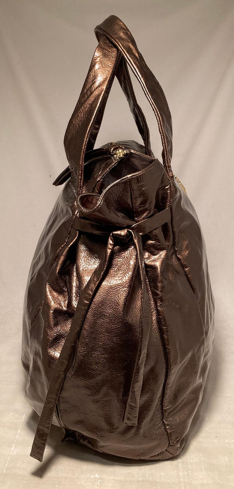 Gucci Bronze Patent Leather Hysteria Bag in excellent condition. Metallic bronze patent leather exterior trimmed with gold hardware, double top handles, front round Gucci medallion in gold, unique side ties and coveted Hysteria design. . Top zipper