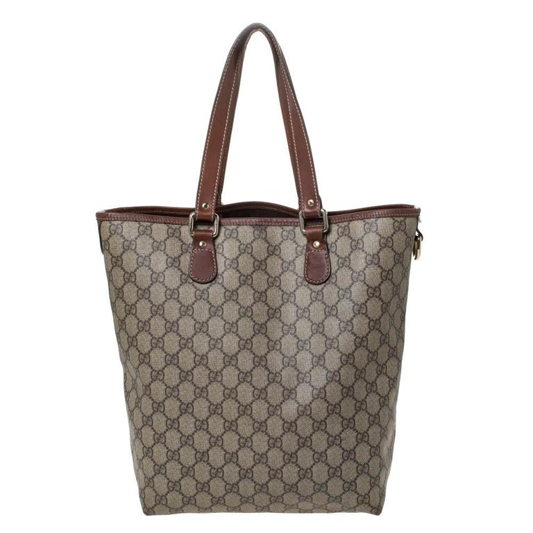 This stylish tote bag by Gucci has been crafted to assist you with ease and style on all days. It is crafted from high-quality GG Supreme canvas and is designed to be durable. The brown/beige tote features two handles and a spacious fabric