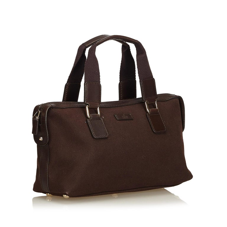 This handbag features a canvas body with leather trim, flat nylon handles, top zip closure, and interior zip and open pockets. It carries as AB condition rating.  Inclusions:  Dust Bag  Dimensions: Length: 17.00 cm Width: 33.00 cm Depth: 10.50