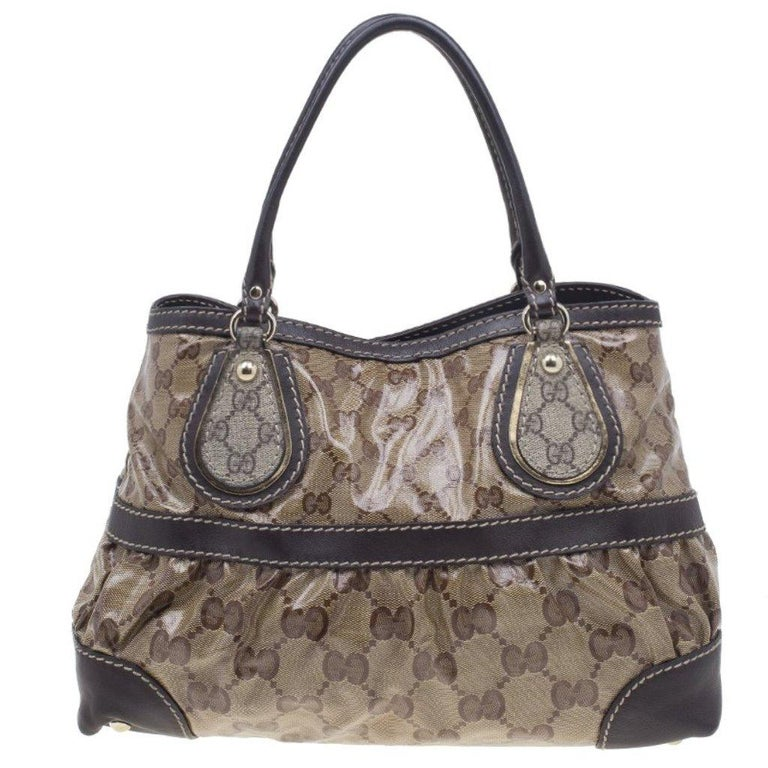 Classically printed and great for daytime, this Crytal Mix Tote by Gucci is a wardrobe must! This medium tote is crafted from beige GG coated canvas with brown leather trim. The everyday look is completed with leather handles and light gold-tone