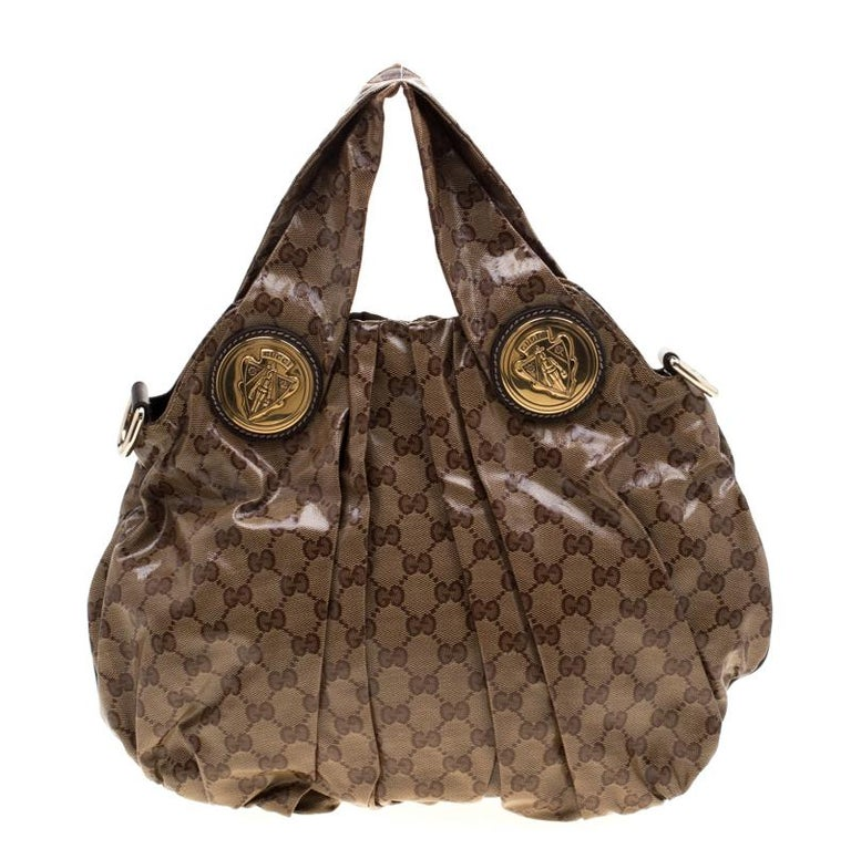 This Gucci hobo is built for everyday use. Crafted from GG crystal canvas, it has a brown exterior and two handles for you to easily parade it. The nylon insides are sized well and the Hysteria hobo is complete with the signature emblems in