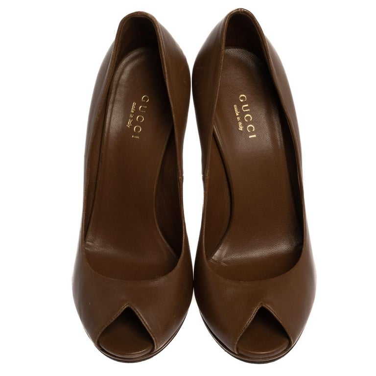 Perfect for formal ensembles as well as casual dresses, these Elizabeth pumps from Gucci will prove to be an amazing addition to your wardrobe. The brown pumps are crafted from leather and feature a peep-toe silhouette. They flaunt the signature