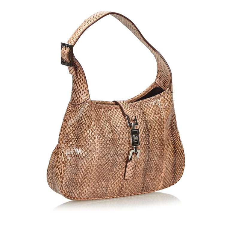 This shoulder bag features a python leather body, a flat strap, an open top with a leather top strap, and an interior zip pocket. It carries as B+ condition rating.  Inclusions:  Dust Bag  Dimensions: Length: 15.00 cm Width: 20.00 cm Depth: 4.00