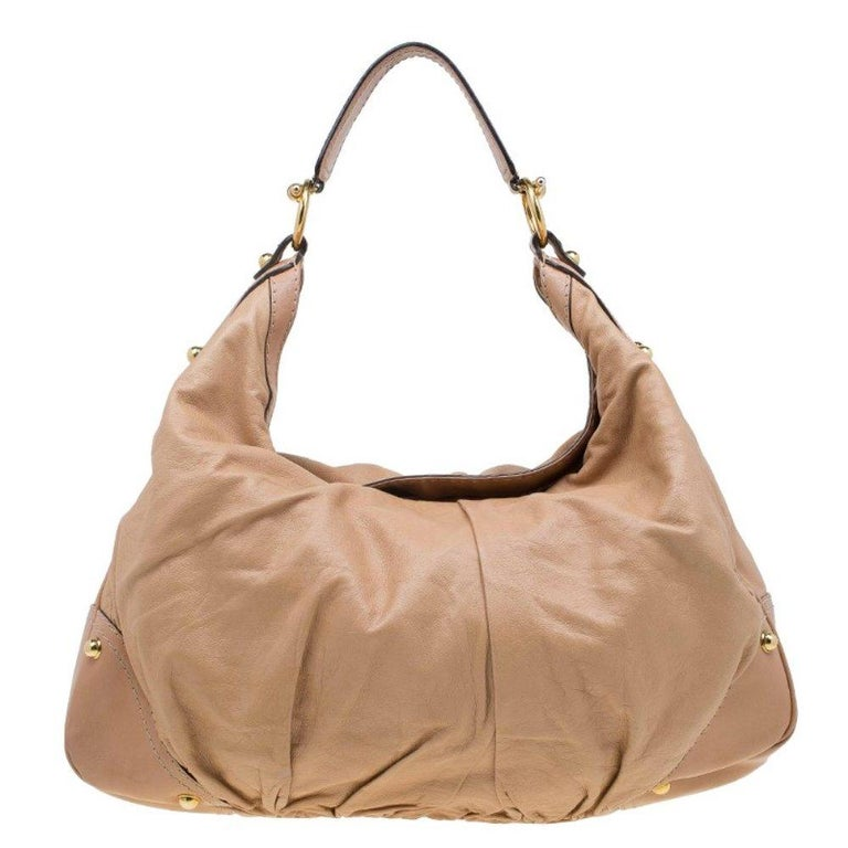 The Jockey hobo by Gucci is both glamorous and chic. Its body is crafted in leather, featuring a non-adjustable strap with rings and gold-tone hardware. The interior is lined with monogrammed nylon and features a cell phone pocket and a zip pocket